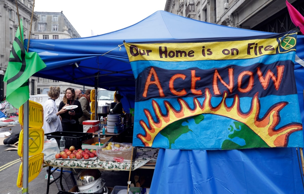 A temporary food stall serves the demostrators as the road is blocked during a climate protest at Oxford Circus in London, Tuesday, April 16, 2019. The group Extinction Rebellion is organizing a week of civil disobedience against what it says is the failure to tackle the causes of climate change. (AP Photo/Kirsty Wigglesworth)