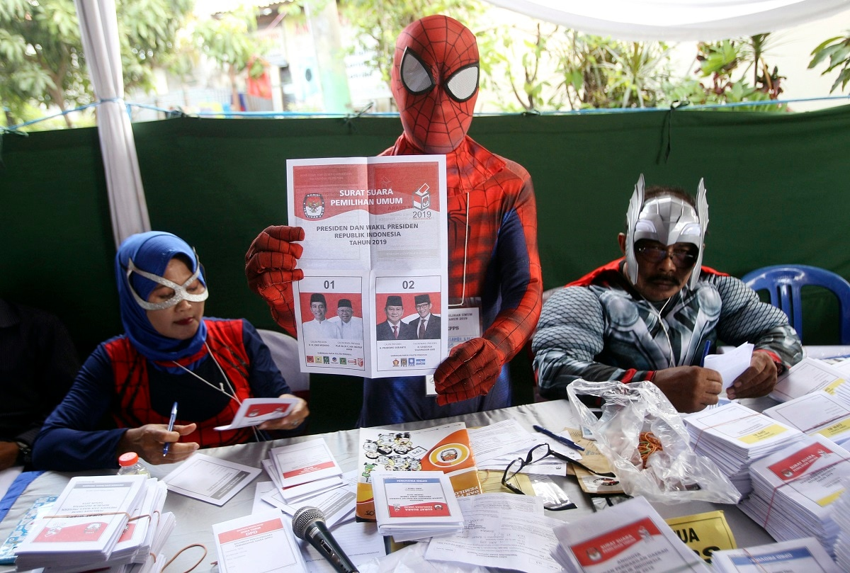 Electoral workers in superhero costumes show presidential ballot during the election at a polling station in Surabaya, Indonesia. (AP Photo/Trisnadi))