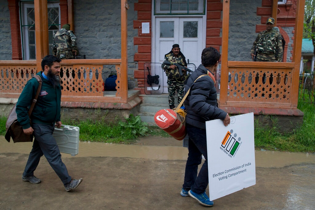 Kashmiri polling officials carry electronic voting machines and other election material on the eve of the second phase of general election outside a distribution centre in Srinagar, Jammu and Kashmir, Wednesday, April 17, 2019. (AP Photo/Dar Yasin)
