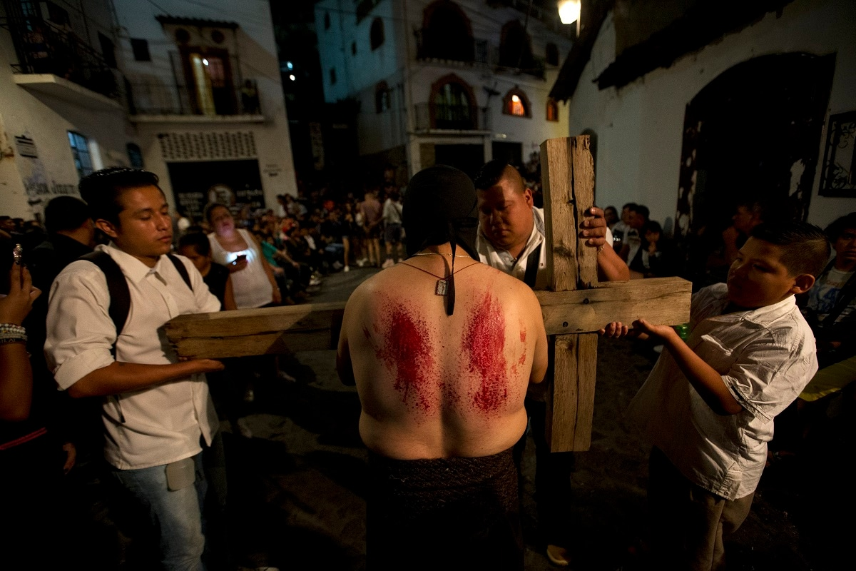 Men accompanying a penitent help him to take up his cross again after pausing to flog himself with a nail-studded whip, during a Holy Week procession of penitents in Taxco, Mexico. In traditional processions that last from Thursday evening into the early morning hours of Friday, hooded penitents drag chains and shoulder bundles of thorny branches through the streets, while others flog themselves with nail-studded whips meant to bring them closer to God. (AP Photo/Rebecca Blackwell)