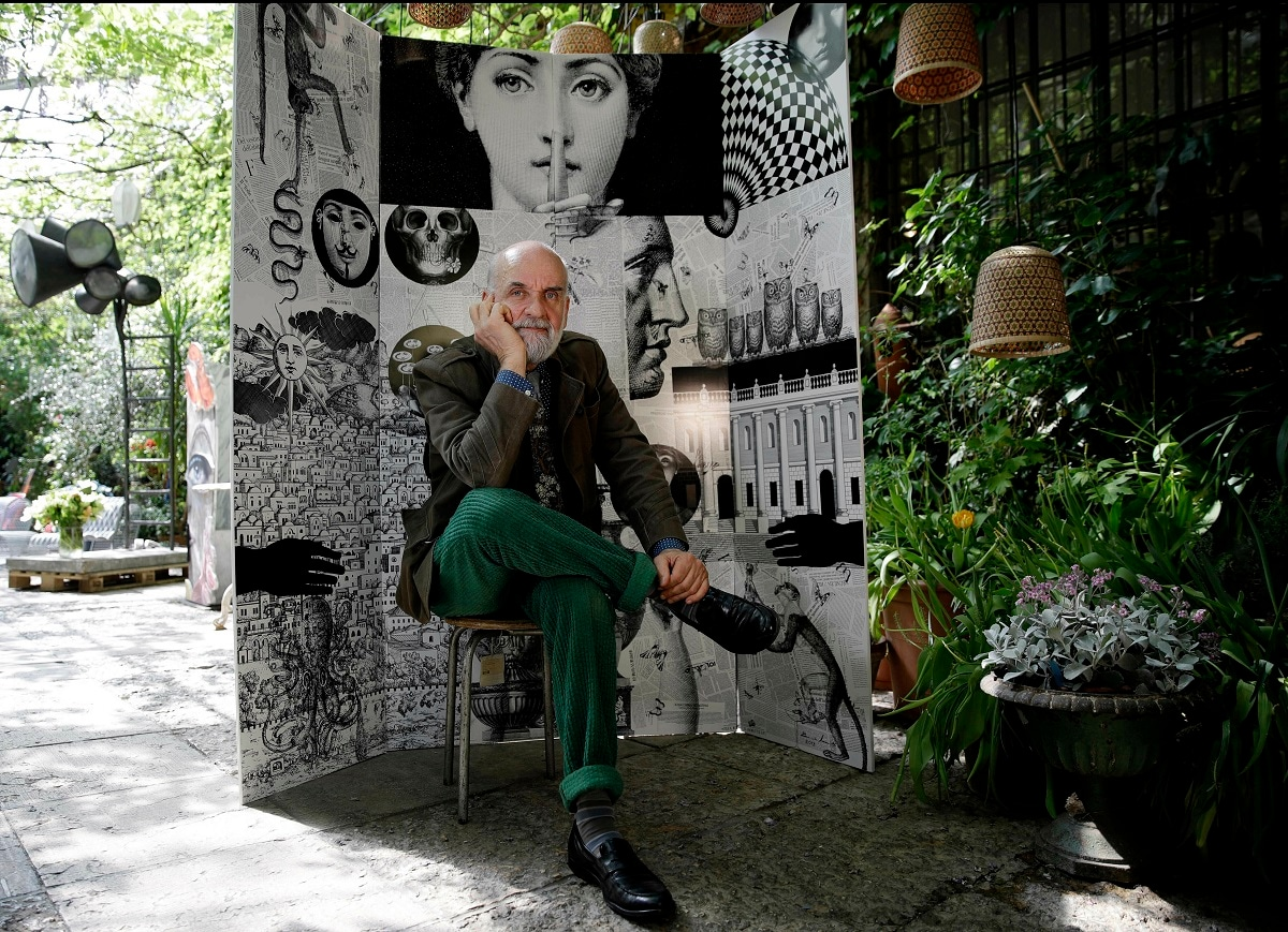 Design artistic director Barnaba Fornasetti poses in front of a paravent folding screen 'Fornasettiana Remix', made with regenerated polystyrene, for the