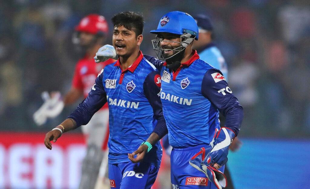 Delhi Capitals players Sandeep Lamichhane, left and Rishabh Pant celebrate the dismissal of Kings XI Punjab batsman Chris Gayle during VIVO IPL cricket T20 match in New Delhi, India, Saturday, April 20, 2019. (AP Photo/Altaf Qadri)