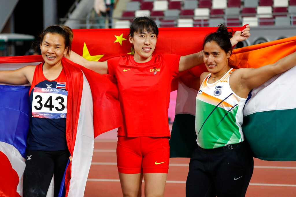 Gold medalist Lyu Huihui of China, centre, celebrates with silver medalist Natta Nathan of Thailand, left, and bronze medalist Annu Rani of India after competing in their women's javelin throw final during the 23rd Asian Athletics Championships in Doha, Qatar, Sunday, April 21, 2019. (AP Photo/Vincent Thian)