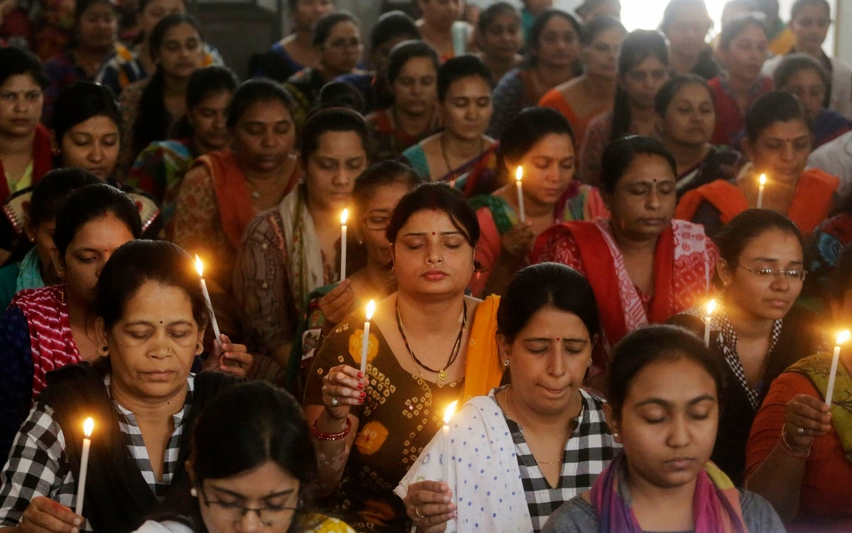 Staff at a school pray for the victims of Sunday's blasts in Sri Lanka, in Ahmadabad. (AP Photo/Ajit Solanki)