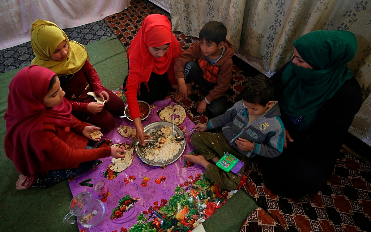 Um Yusuf and her children have lunch, in Mosul. (AP Photo/Farid Abdulwahed)