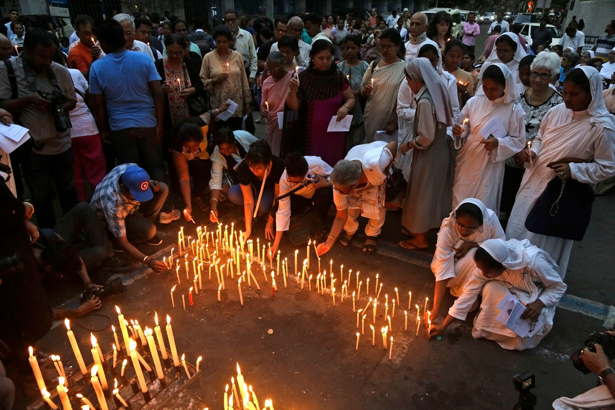 Catholic nuns and others light candles during a prayer meeting for victims of Sunday's bombings in Sri Lanka, in Kolkata. (AP Photo/Bikas Das)