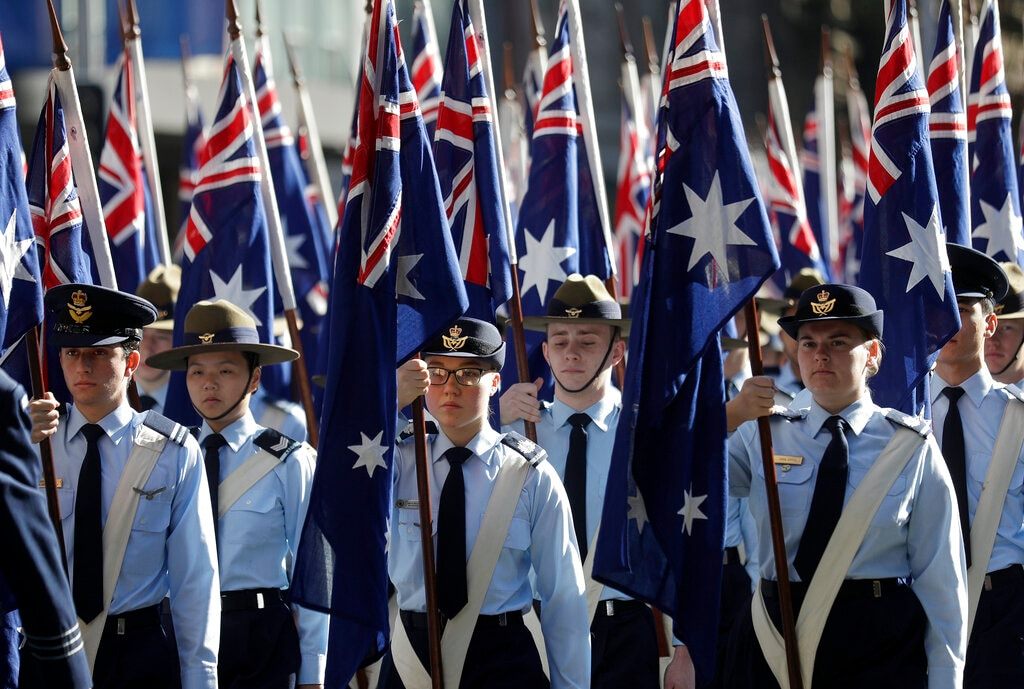 Flag bearers carry Australian flags during a march celebrating ANZAC Day, a national day of remembrance in Australia and New Zealand that commemorates those that served and died in all wars, conflicts, and while peacekeeping, in Sydney, Australia, Thursday, April 25, 2019. (AP Photo/Rick Rycroft)
