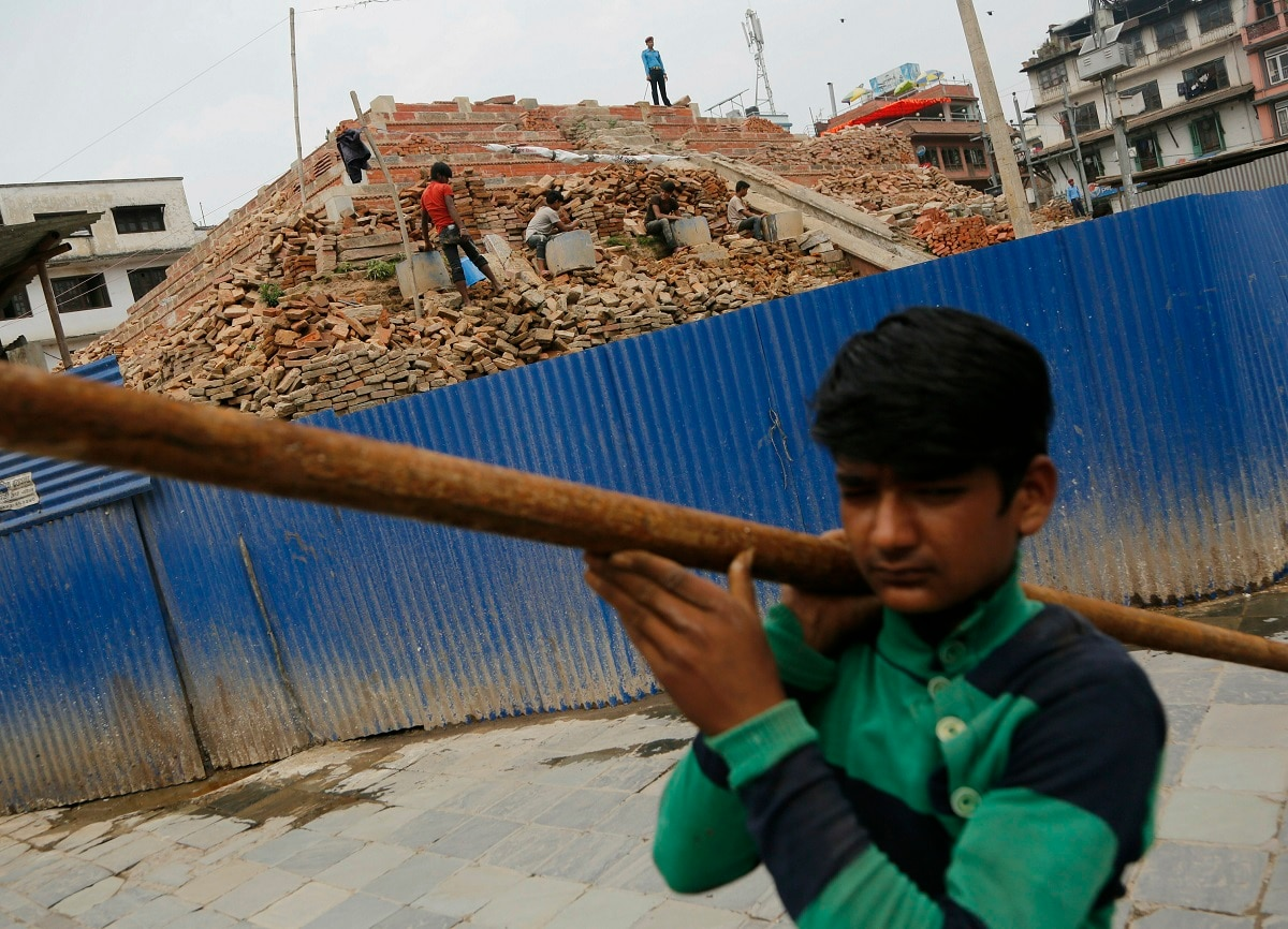 A Nepalese reconstruction labourer works on a reconstruction site in Basantapur Durbar square on the anniversary of the 2015 earthquake, in Kathmandu. The violence of the 7.8-magnitude earthquake killed nearly 9,000 people and left countless towns and villages across central Nepal in shambles. (AP Photo/Niranjan Shrestha)