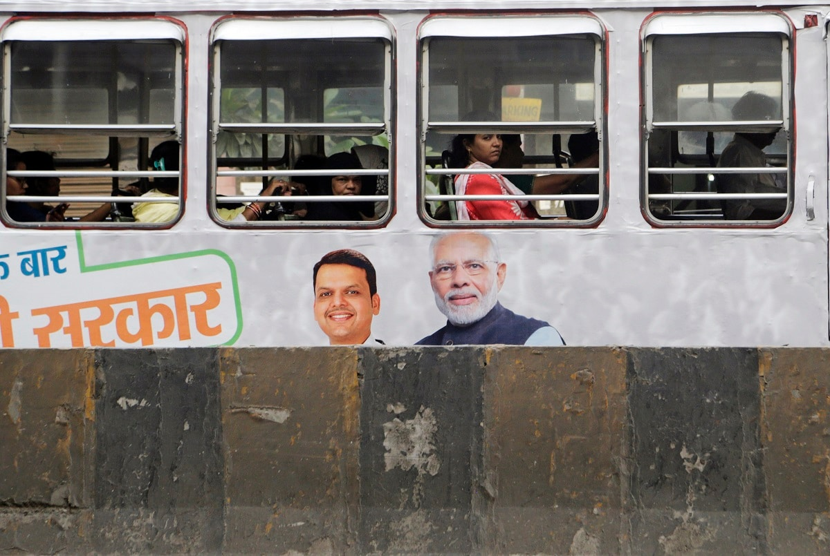 Passengers look out from the window of a bus painted with a portrait of Prime Minister Narendra Modi and Maharashtra state Chief Minister Devendra Fadnavis in Mumbai. (AP Photo/Rajanish Kakade)