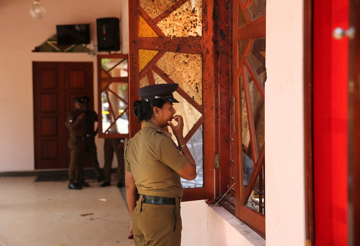 A Sri Lankan policewoman looks at the damage inside St. Sebastian's Church, one of the sites of Easter Sunday's bombings, in Negombo, north of Colombo, Sri Lanka.  (AP Photo/Manish Swarup)