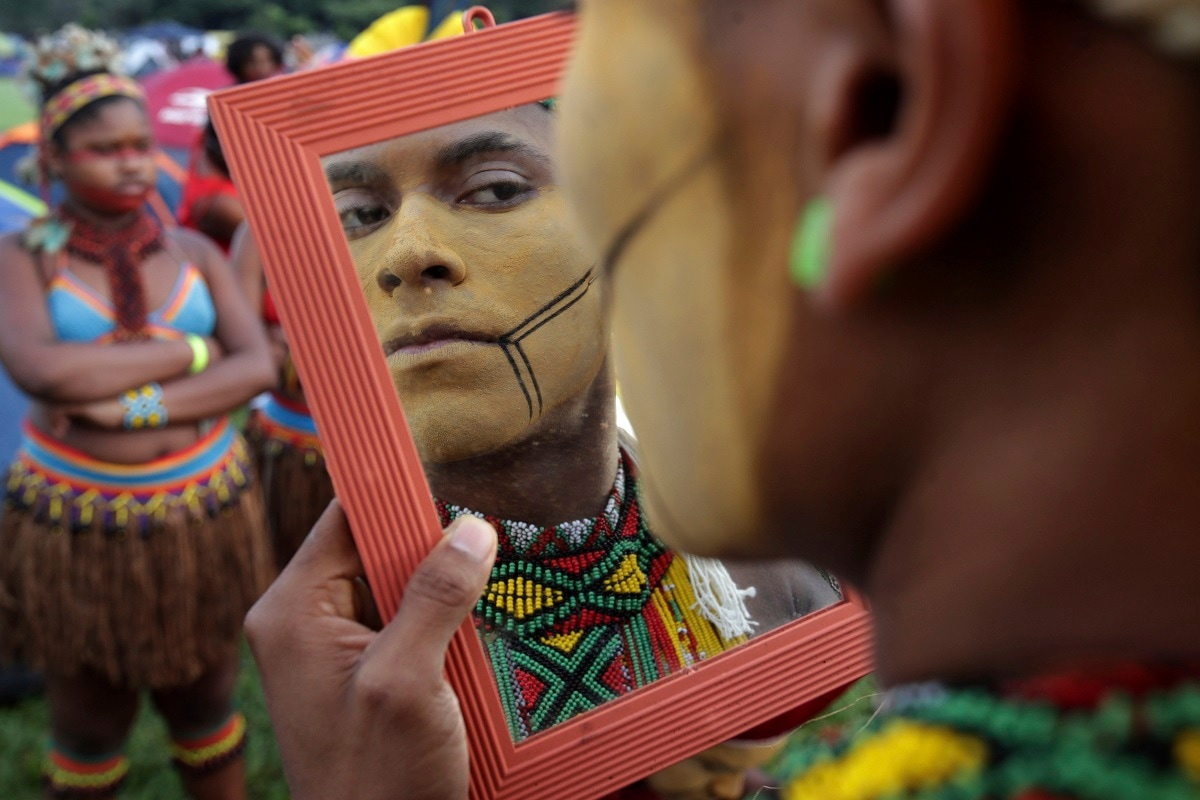 A young indigenous man applies body paint as he checks himself out in a mirror, during an annual three-day campout protest known as the Free Land Encampment, in Brasilia, Brazil. The event begins amid animosity between Brazil's indigenous groups and the new government of far-right President Jair Bolsonaro. (AP Photo/Eraldo Peres)