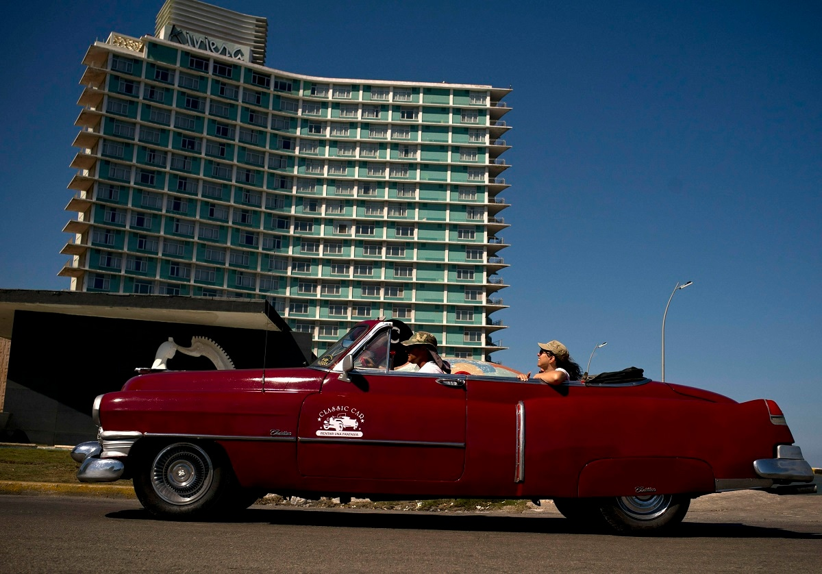 A vintage American car carries tourists next to hotel Riviera, managed by the Spanish company Iberostar, in Havana, Cuba. The European Union ambassador to Cuba says the Trump administration's crackdown on business with the communist government is causing unprecedented concern among European companies doing business on the island. (AP Photo/Ramon Espinosa)