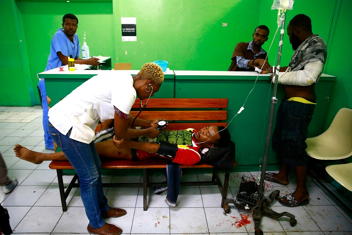 Jean Renel Joseph is tended too at the General Hospital emergency room after he was shot, in Port-au-Prince, Haiti. Renel Joseph was shot last night while sitting with his friends near his home. Armed men open fire into the crowd and killed several people in the Carrefour-Feuille district of Port-au-Prince. (AP Photo/Dieu Nalio Chery)