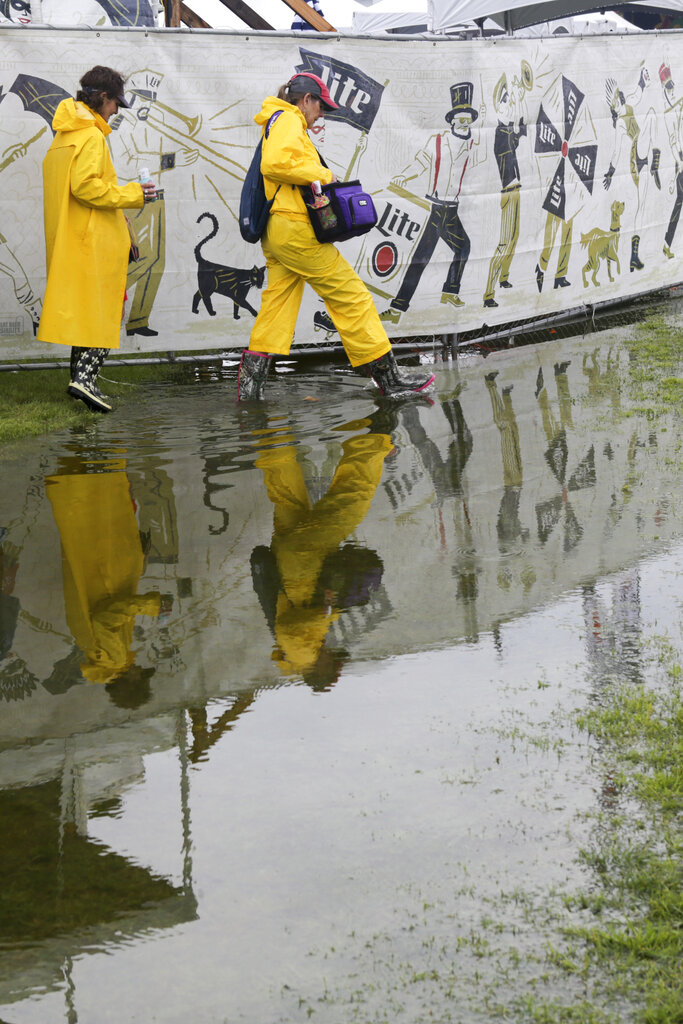 Festival-goers wear rain gear as they roam the flooded grounds at the New Orleans Jazz & Heritage Festival New Orleans, Thursday, April 25, 2019. The opening was delayed by heavy rain. (AP Photo/Doug Parker}