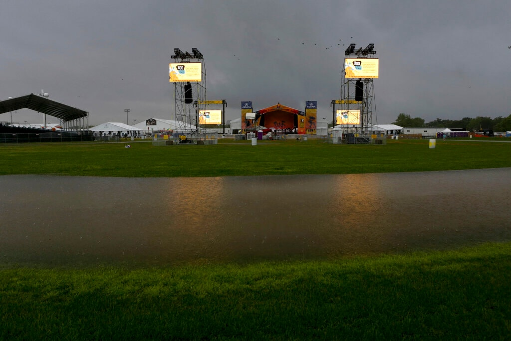 Storm clouds hover over the Acura stage at the New Orleans Jazz & Heritage Festival in New Orleans, Thursday, April 25, 2019. (AP Photo/Doug Parker}