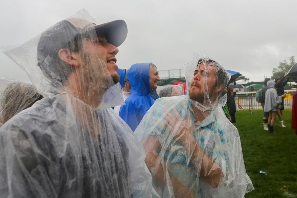 Festival-goers Joe Spotam left, and Brandon Bushnell, both of California, wear ponchos at the New Orleans Jazz & Heritage Festival New Orleans, Thursday, April 25, 2019. The opening was delayed by heavy rain. (AP Photo/Doug Parker}