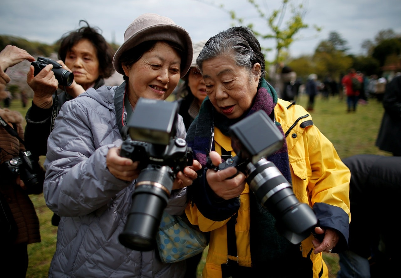 Royal aficionado Fumiko Shirataki, 78, and her friend show each other photographs they took of Japan's Emperor Akihito and Empress Michiko who passed in front of them at Kodomonokuni in Yokohama, south of Tokyo, Japan, April 12, 2019. (Reuters)