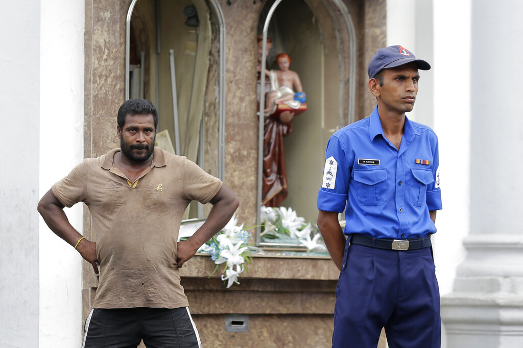 A Sri Lankan police officer and a local stand outside St. Anthony's Shrine where a blast happened in Colombo, Sri Lanka, Sunday, April 21, 2019. A Sri Lanka hospital spokesman says several blasts on Easter Sunday have killed dozens of people. (AP Photo/Eranga Jayawardena)