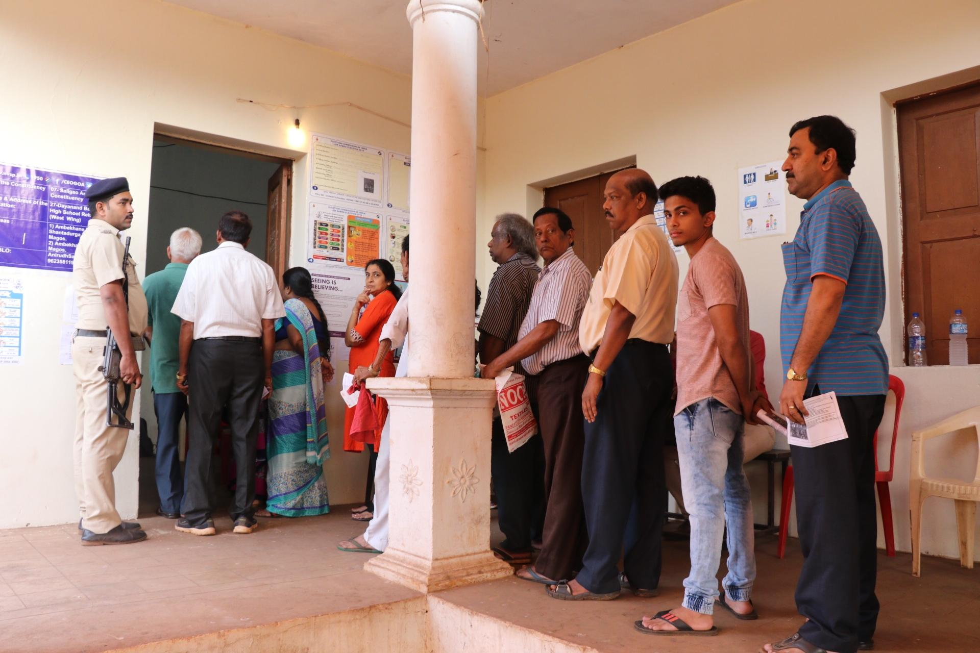 People stand in a queue to cast their vote for Lok Sabha elections at a polling booth in Verem, North Goa on April 23, 2019. (Photo: IANS)