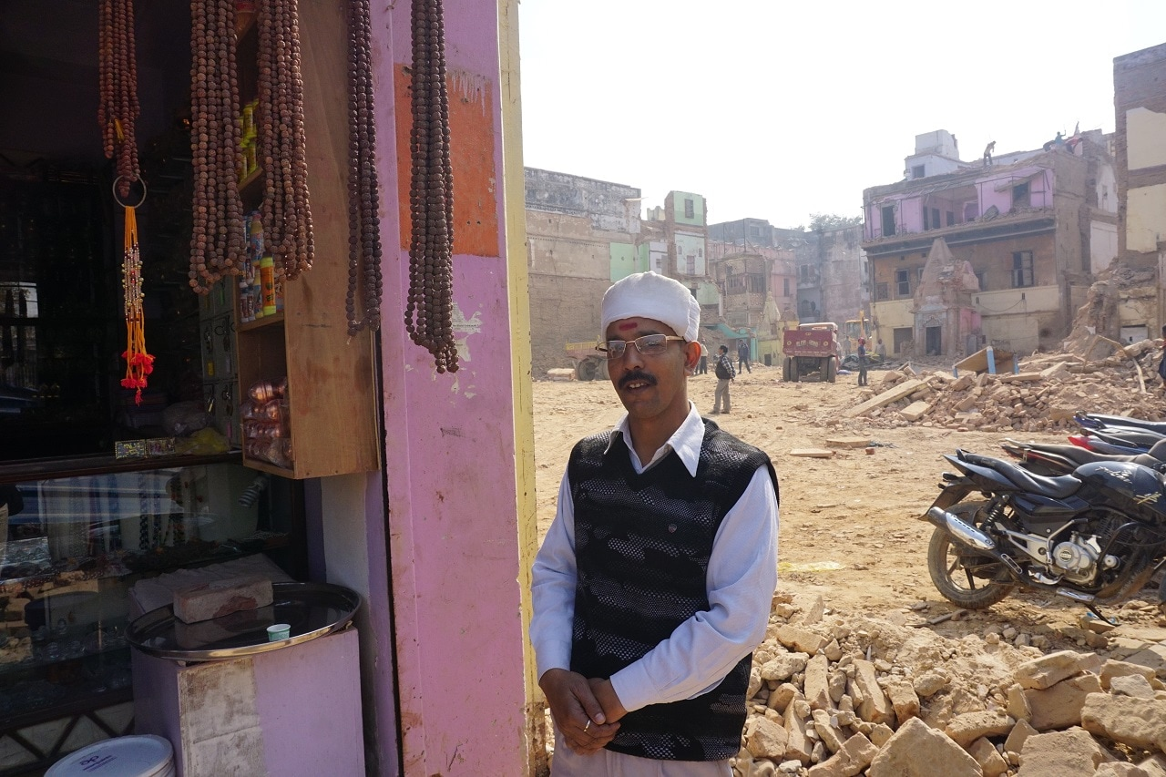 A man stands near the demolished temple near to the Kashi Vishwanath Temple, Varanasi in Uttar Pradesh.