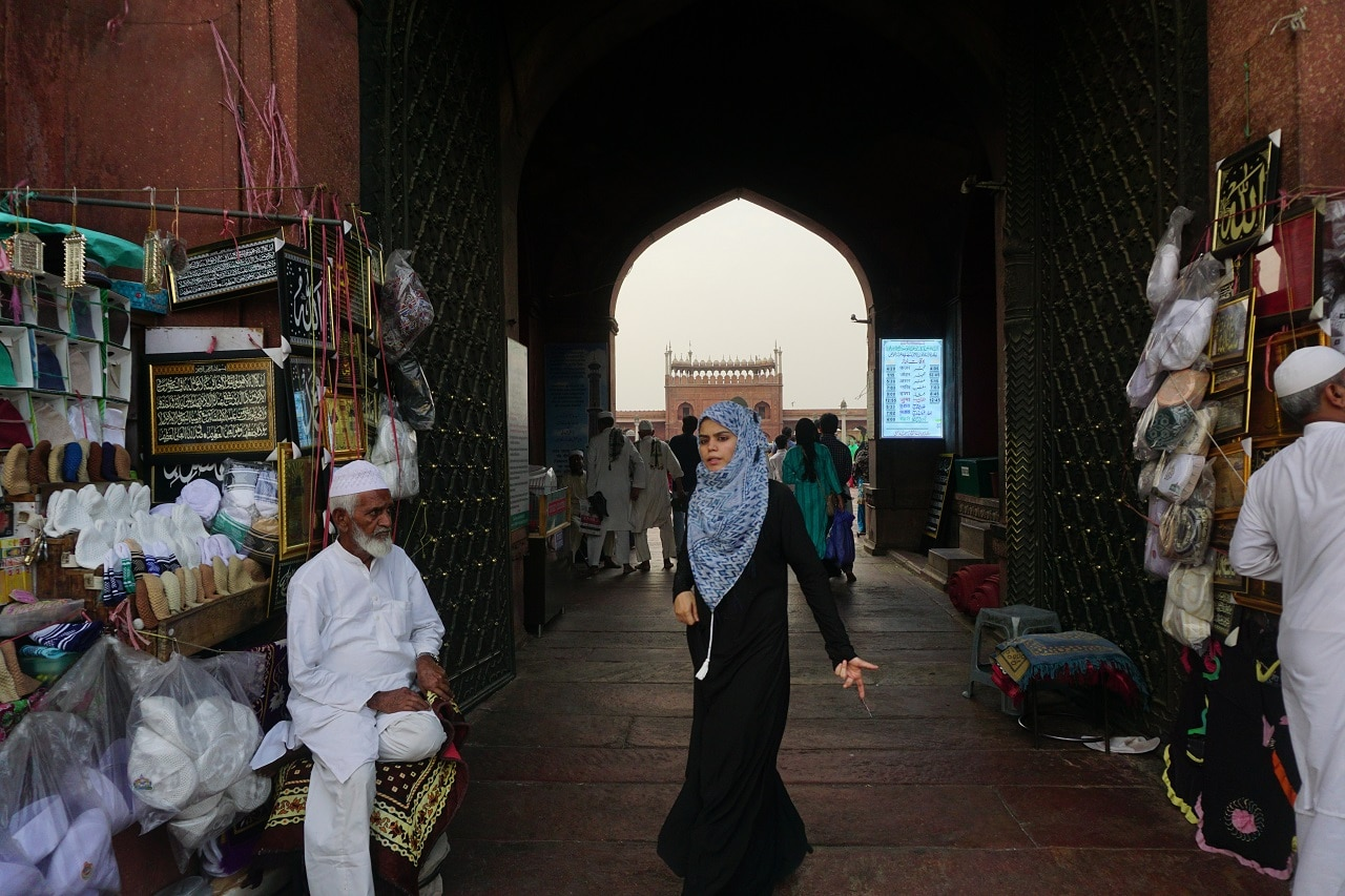 A woman walks past the Jama Masjid (Grand Mosque) in the old quarters of Delhi