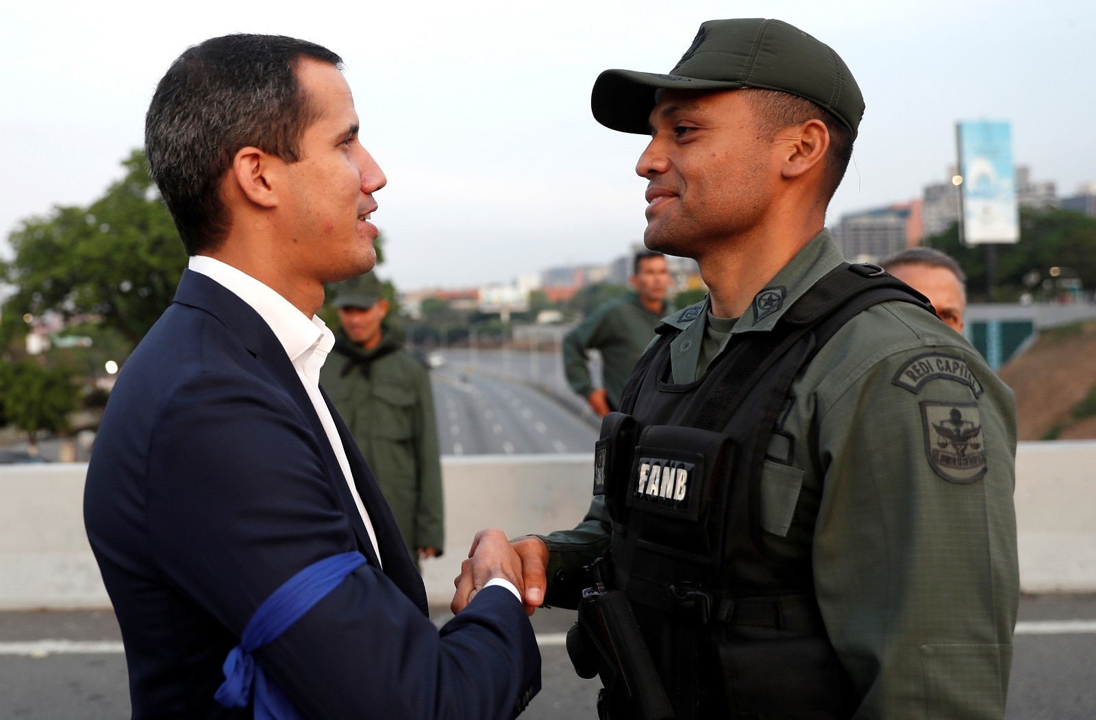 Venezuelan opposition leader Juan Guaido, who many nations have recognised as the country's rightful interim ruler, shakes hands with a military member near the Generalisimo Francisco de Miranda Airbase