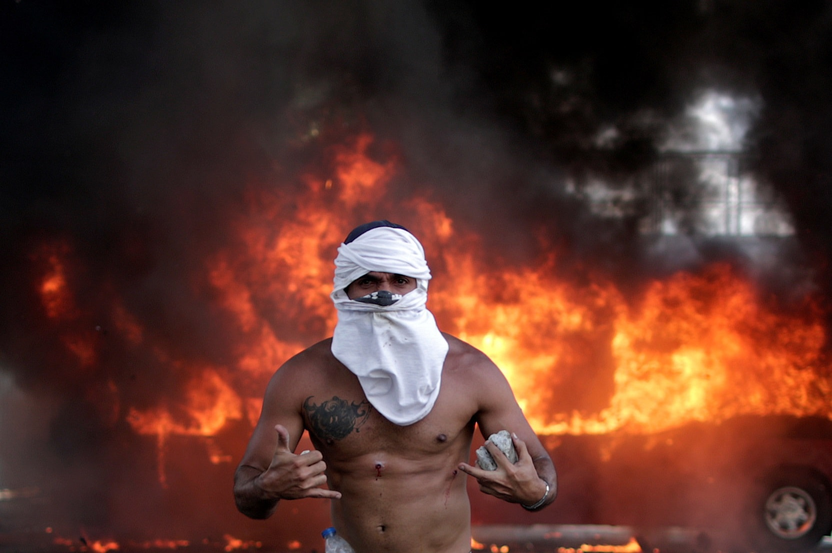 An opposition demonstrator with wounds gestures in front of a burning bus, while holding a rock, near the Generalisimo Francisco de Miranda Airbase