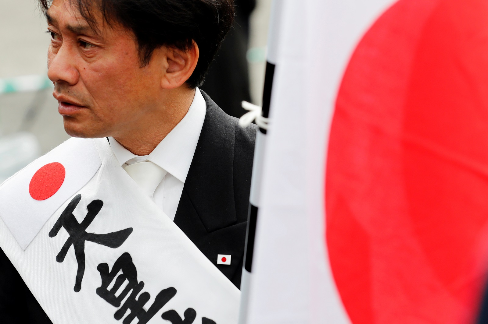 A man holds a Japanese flag while waiting for the arrival of Japan's new Emperor Naruhito to the Imperial Palace in Tokyo, Japan May 1, 2019. REUTERS/Kim Kyung-Hoon