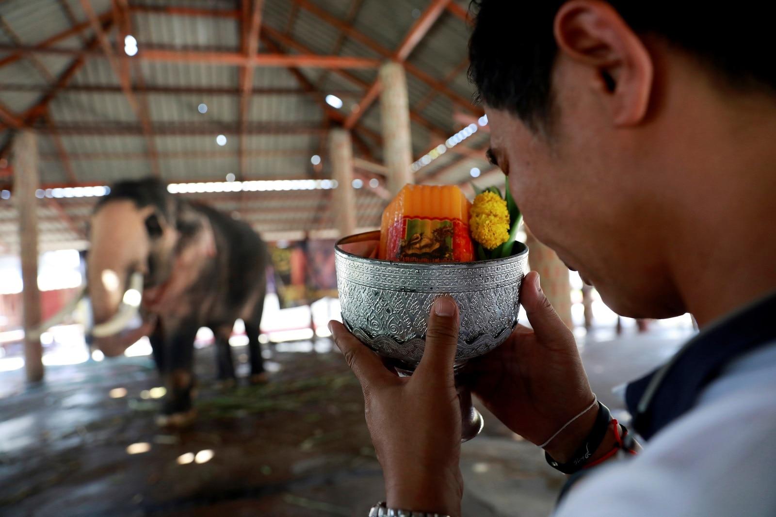 A man makes an offering to Plai Ekachai, 33, in Maha Sarakham, Thailand April 25, 2019. REUTERS/Soe Zeya Tun