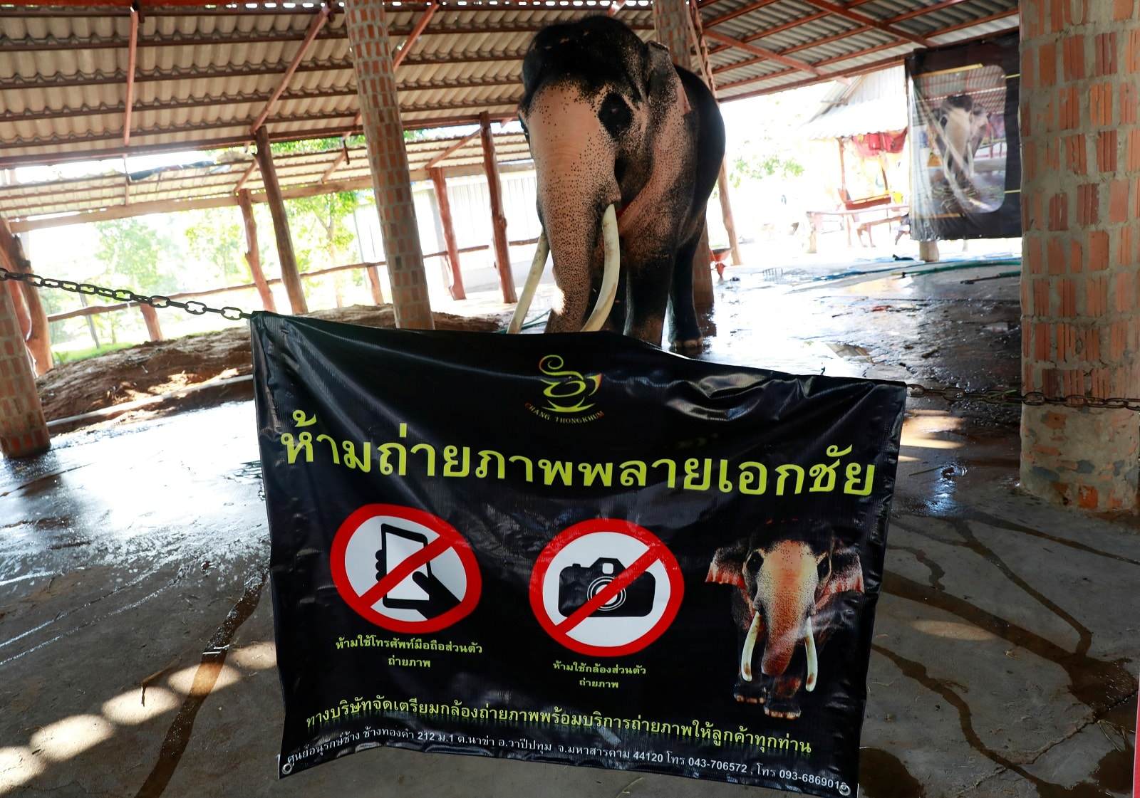 Plai Ekachai, 33 is seen in Maha Sarakham, Thailand April 25, 2019. The sign in front of him reportedly reads no photography. REUTERS/Soe Zeya Tun