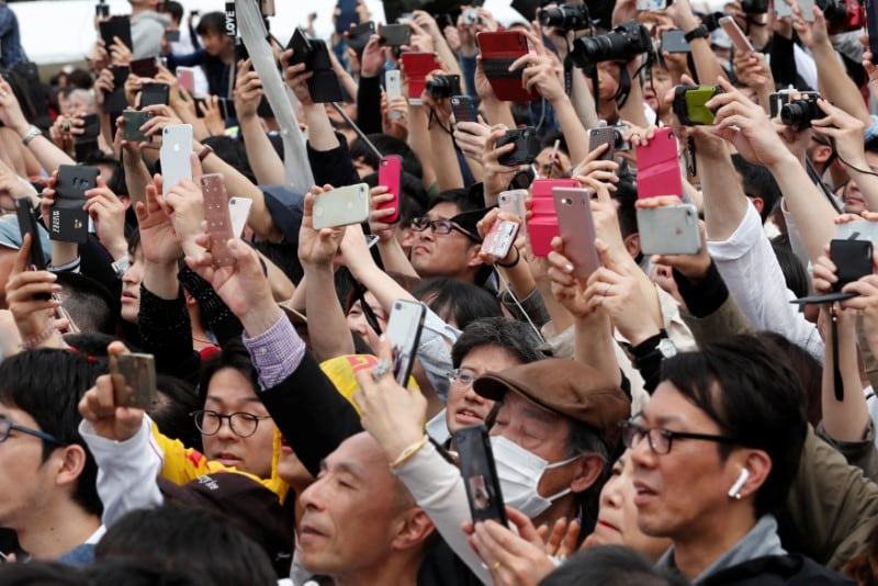 People take pictures of Japan's Emperor Naruhito as he leaves the Imperial Palace in Tokyo, Japan May 1, 2019. REUTERS/Kim Kyung-Hoon