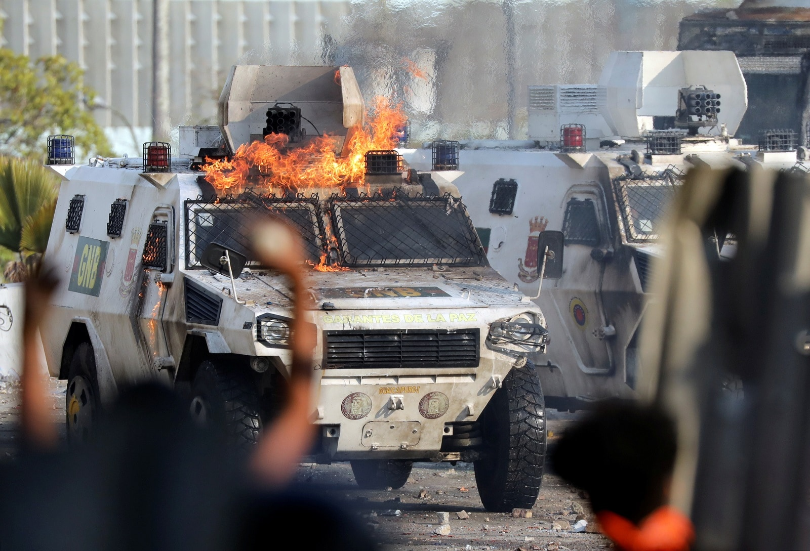 Demonstrators react in front of a burning military vehicle during clashes with security forces in Caracas, Venezuela May 1, 2019. REUTERS/Manaure Quintero