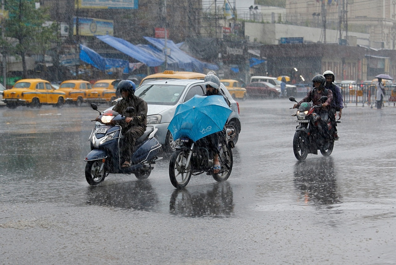 People ride their motorbikes during heavy rains in Kolkata, India, May 3, 2019. (Reuters)