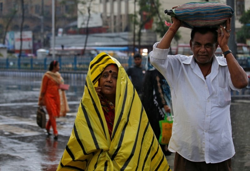 Commuters shelter from the rains as they cross a road in Kolkata, India, May 3, 2019. (Reuters)