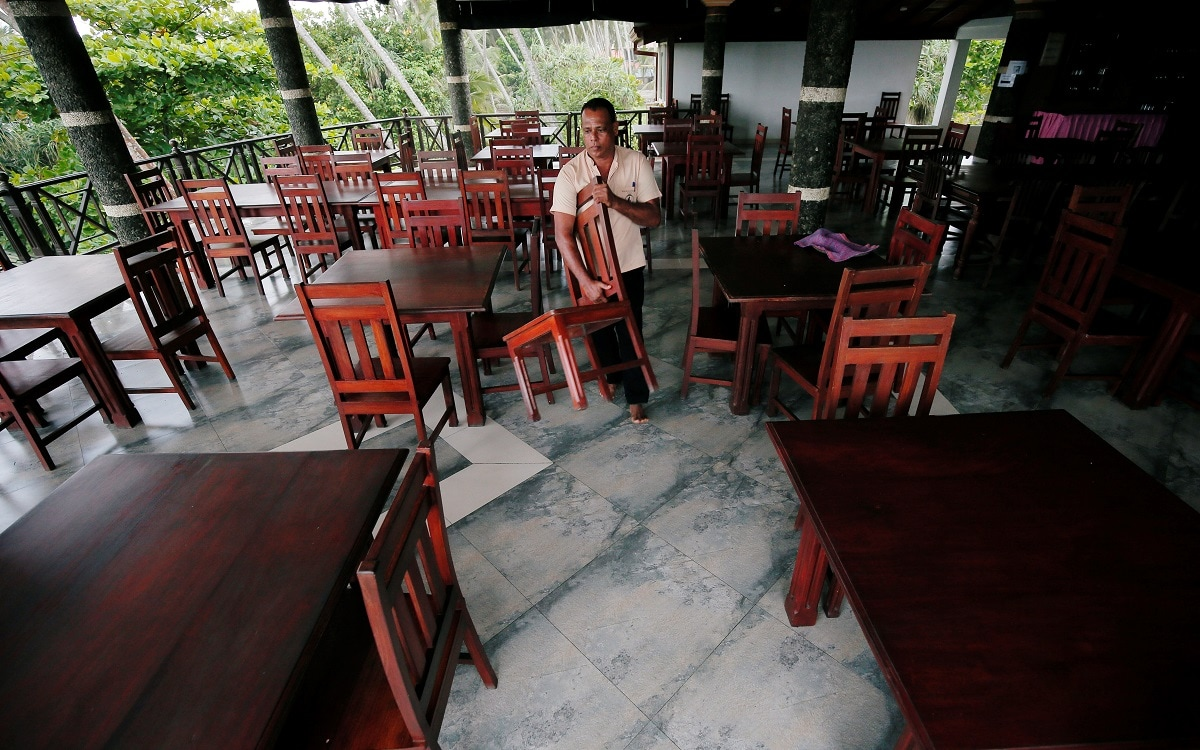 A man arranges chairs at an empty restaurant of the Warahena Beach hotel in Bentota. (REUTERS/Dinuka Liyanawatte)