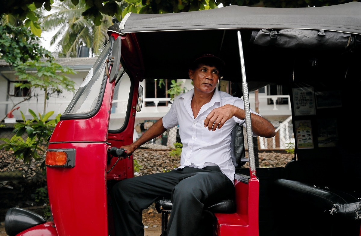 UK Prasanna 54, waits for tourists inside his three-wheeler near a luxury hotel in Bentota. (REUTERS/Dinuka Liyanawatte)