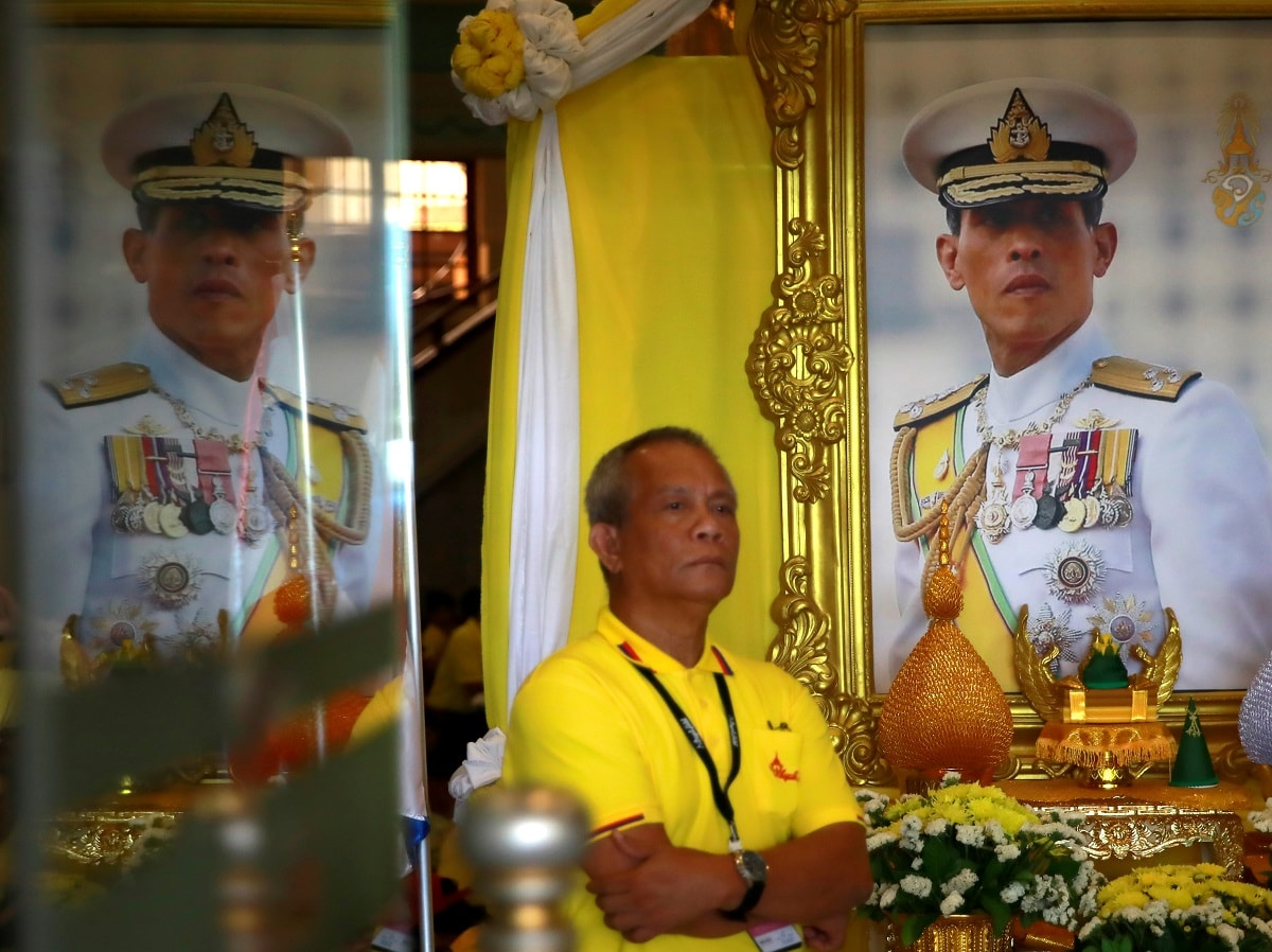 A man stands next to a portrait of Thailand's newly crowned King Maha Vajiralongkorn while waiting for a coronation procession. (REUTERS/Navesh Chitrakar)