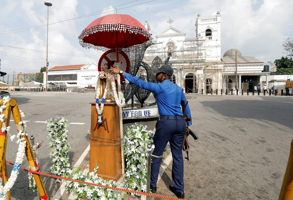 A Sri Lankan navy personnel places a flower garland on a statue of St. Anthony, in front of St. Anthony's Shrine. (REUTERS/Dinuka Liyanawatte)