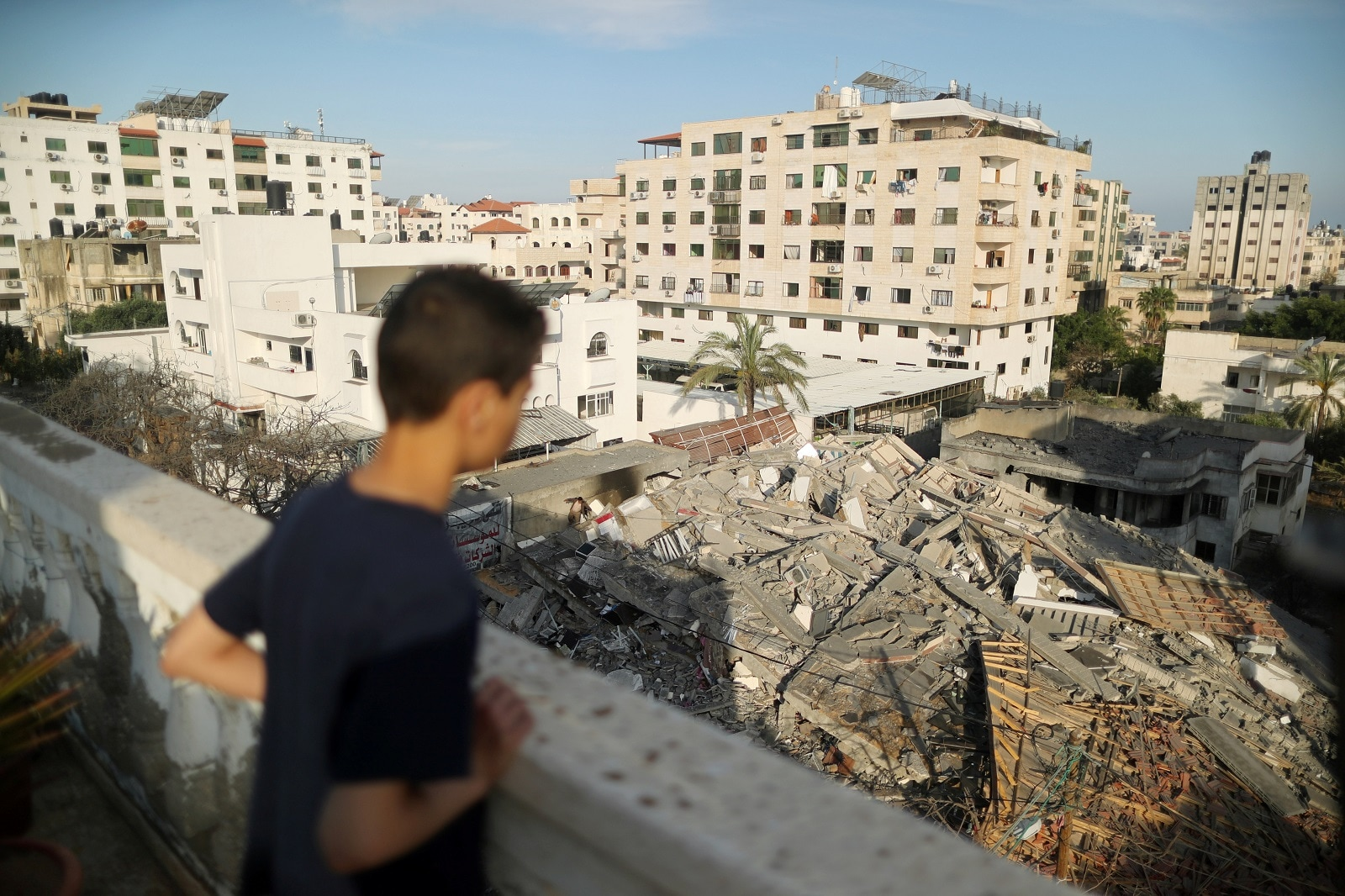 A Palestinian boy looks at the remains of a building that was destroyed in Israeli air strikes, in Gaza City May 5, 2019. REUTERS/Suhaib Salem