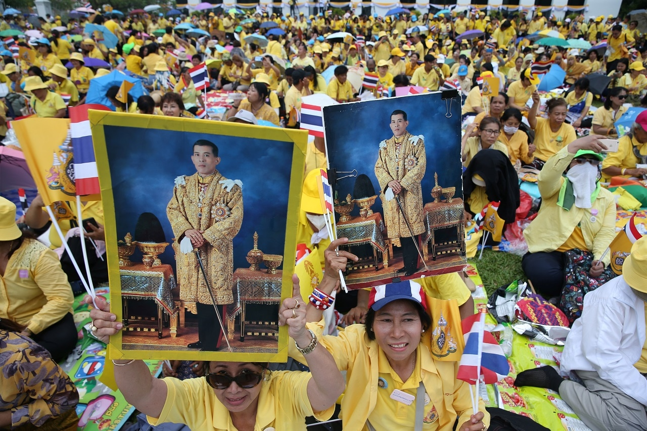 People raise photo of King Maha Vajiralongkorn outside the balcony of Suddhaisavarya Prasad Hall at the Grand Palace, where the King will grant a public audience to receive the good wishes of the people in Bangkok, Thailand May 6, 2019. REUTERS/Athit Perawongmetha