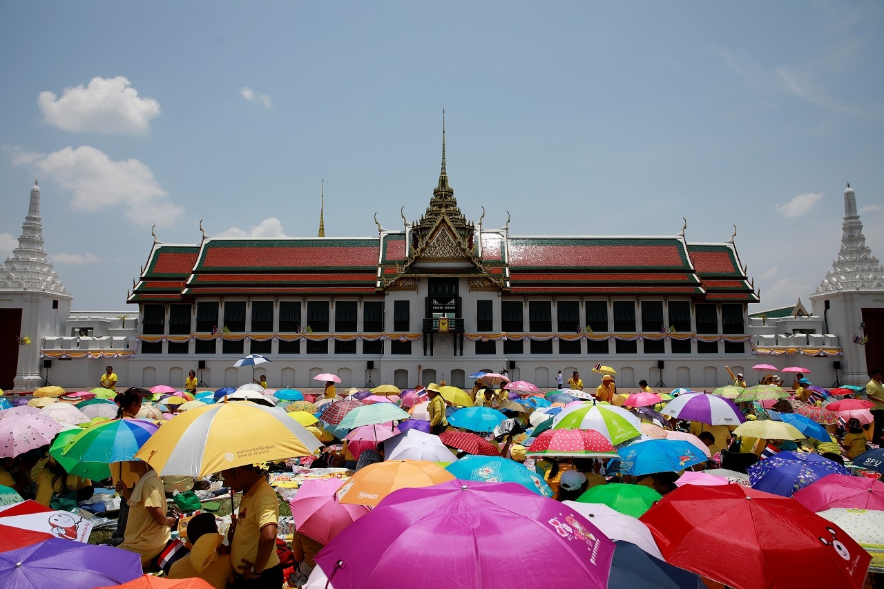 People shelter from the sun with umbrellas at the balcony of Suddhaisavarya Prasad Hall at the Grand Palace where King Maha Vajiralongkorn will grant a public audience to receive the good wishes of the people in Bangkok, Thailand May 6, 2019. REUTERS/Navesh Chitrakar
