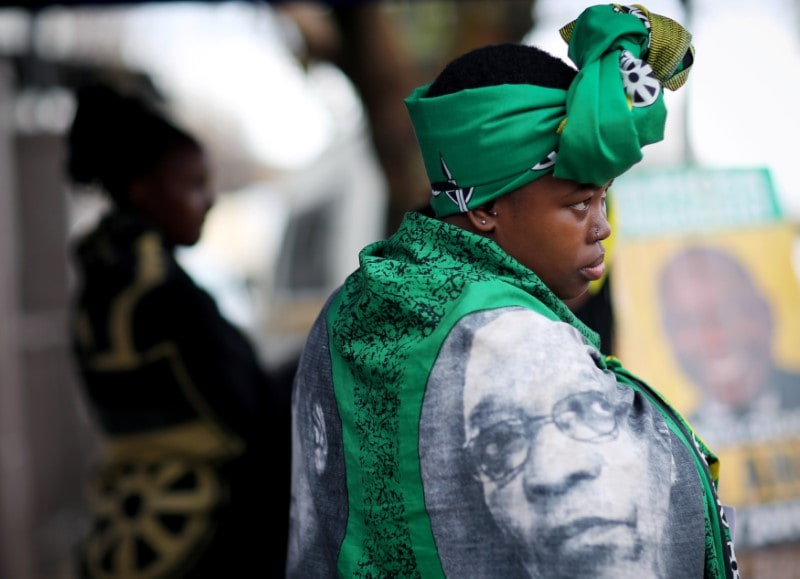An African National Congress (ANC) party volunteer draped in a scarf picturing the face of former President Jacob Zuma, stands outside a voting station during the country's parliamentary and provincial elections in Cape Town, South Africa, May 8, 2019. (Reuters)