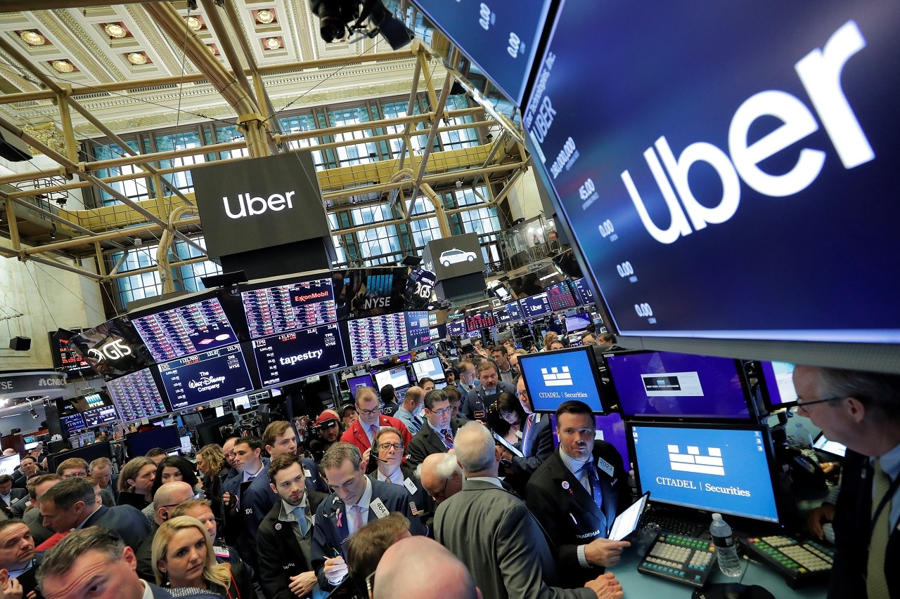 Traders gather at post where Uber Technologies Inc. holds it's IPO on the floor of the New York Stock Exchange (NYSE) in New York, US, May 10, 2019. REUTERS/Brendan McDermid