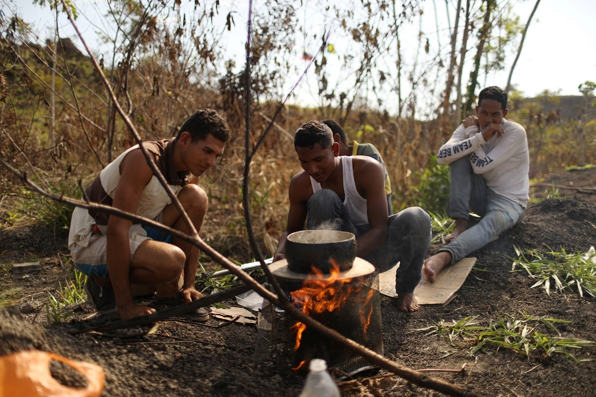 Venezuelan migrants cook on the side of the trail. REUTERS/Pilar Olivares