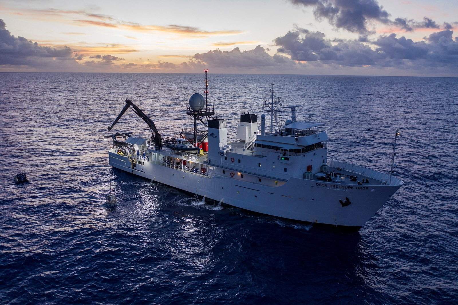 The submarine DSV Limiting Factor is tethered to a crane from the research vessel DSSV Pressure Drop above the Pacific Ocean's Mariana Trench in an undated photo released by the Discovery Channel May 13, 2019. Atlantic Productions for Discovery Channel/Tamara Stubbs/Handout via REUTERS.