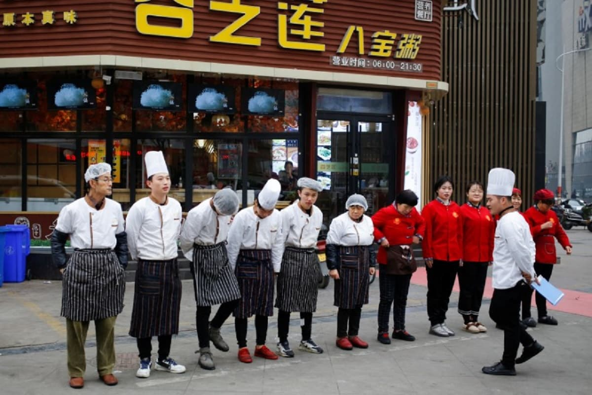 A chef talks to his kitchen staff during their morning assembly outside a restaurant in Zhengzhou, Henan province, China, January 19, 2019. REUTERS/Thomas Peter