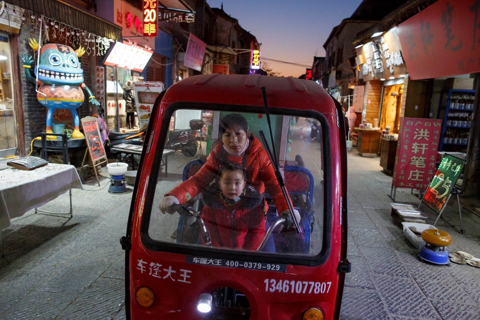 A woman and a child ride an electric tricycle in the old town of Luoyang, Henan province, China January 21, 2019. REUTERS/Thomas Peter