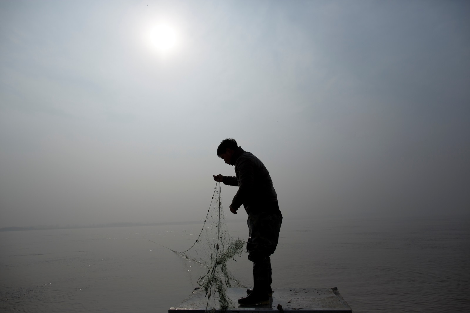 Fisherman Sun Lianxi, 32, stands in a boat as he drops his net into the waters of the Yellow River on the northern outskirts of Zhengzhou, Henan province, China, February 21, 2019. REUTERS/Thomas Peter
