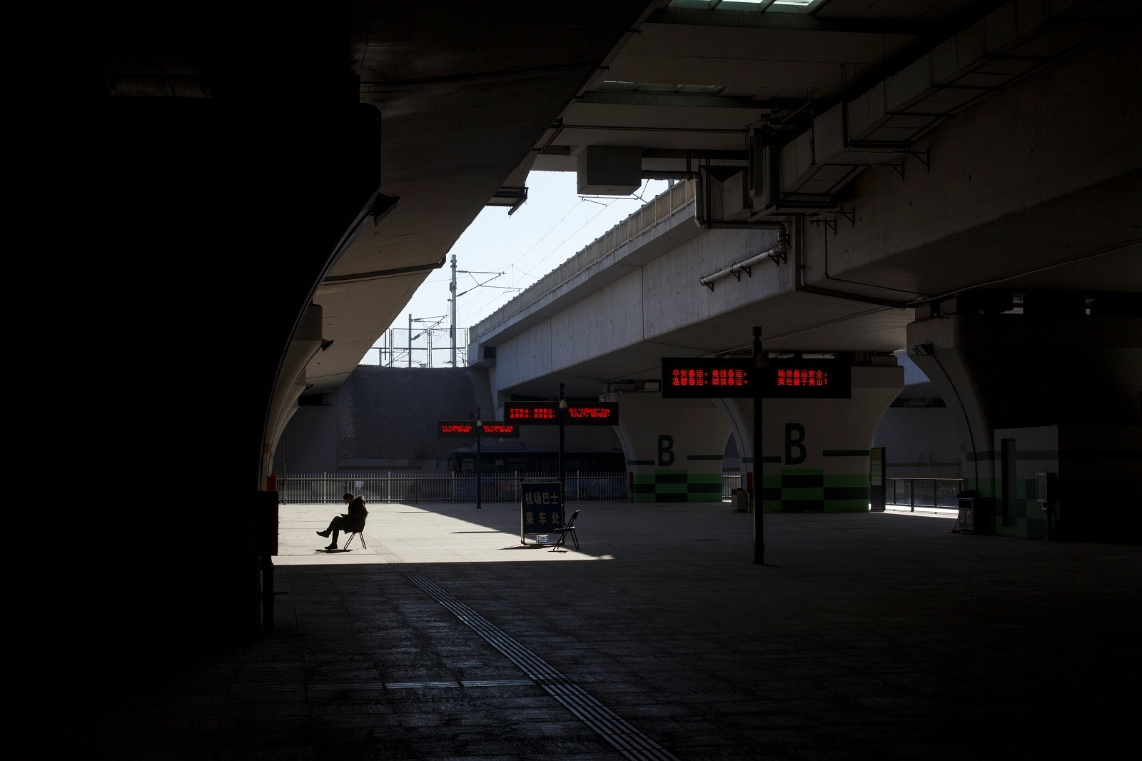 A man waits at a bus stop at a high-speed railway station in Zhengzhou, Henan province China January 22, 2019. REUTERS/Thomas Peter