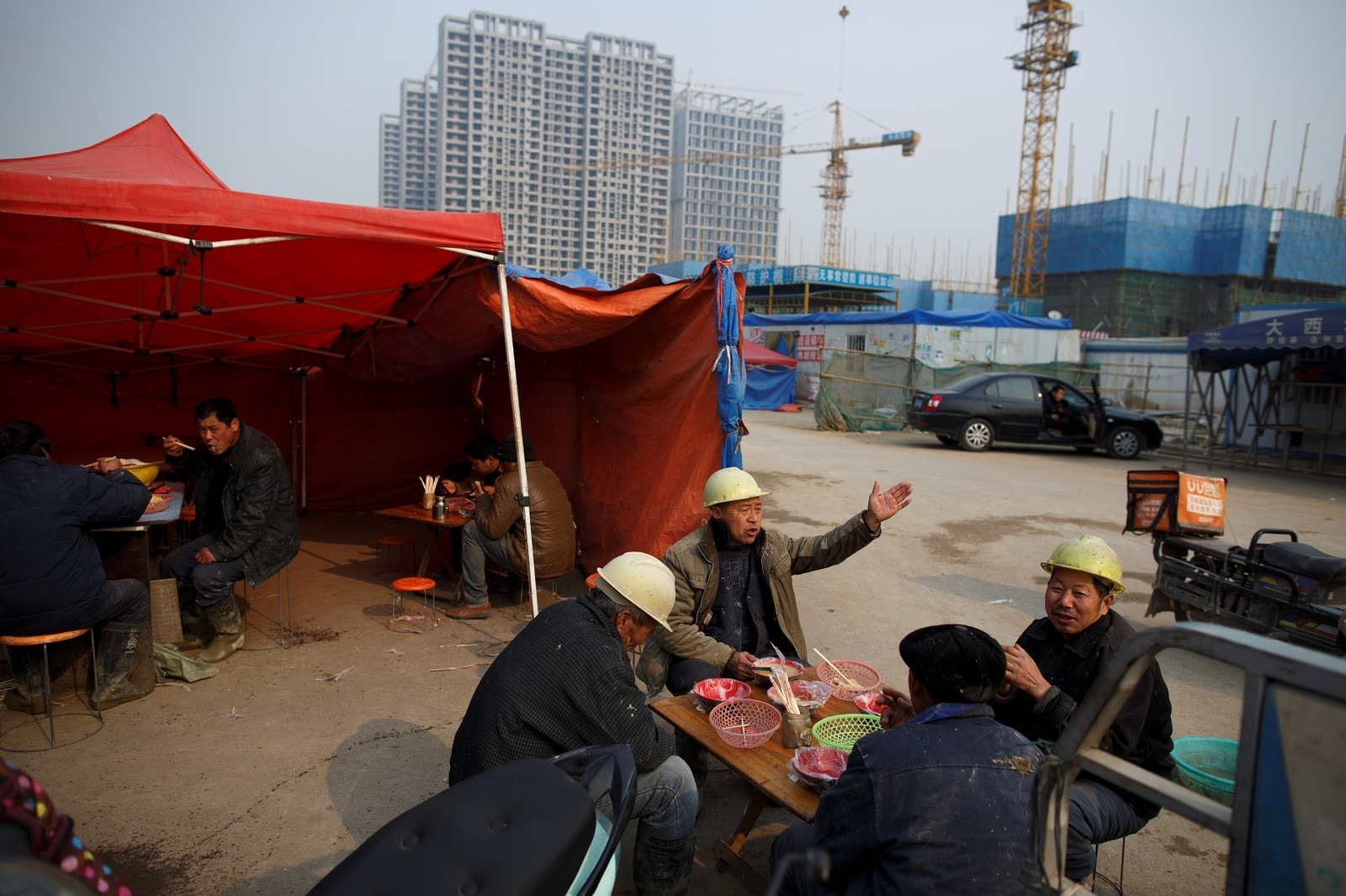 Workers eat lunch near the construction site of apartment buildings near the new stadium in Zhengzhou, Henan province, China January 19, 2019. REUTERS/Thomas Peter